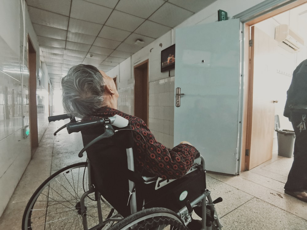 woman in black and white long sleeve shirt sitting on black wheelchair
