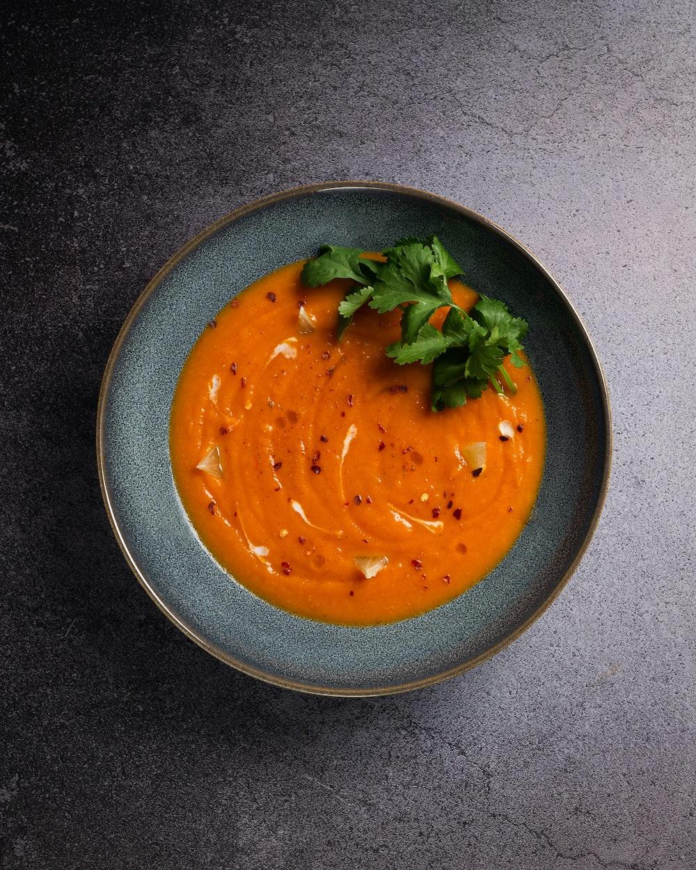 orange soup in black ceramic bowl