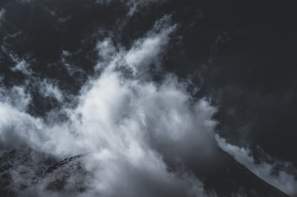 grayscale photo of clouds and mountain
