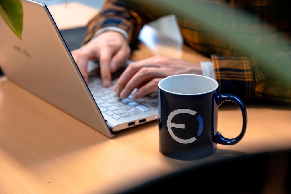 black and white ceramic mug beside macbook pro