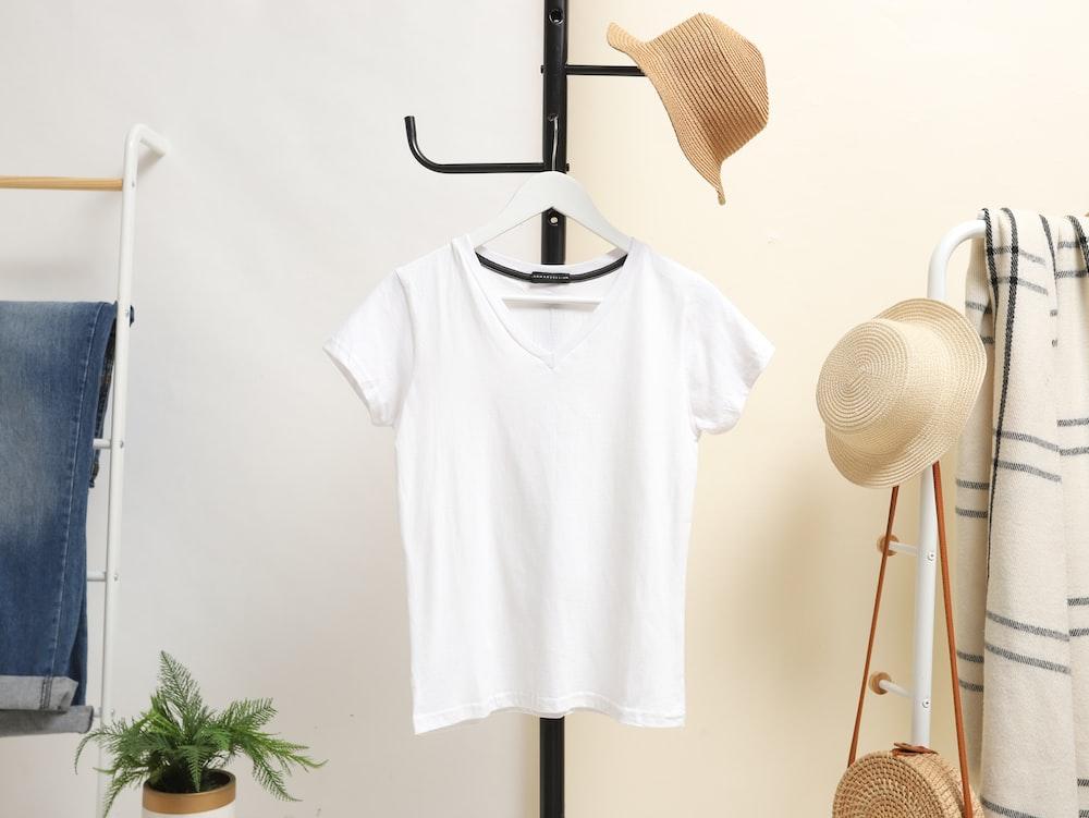 white crew neck t-shirt hanged on black clothes hanger