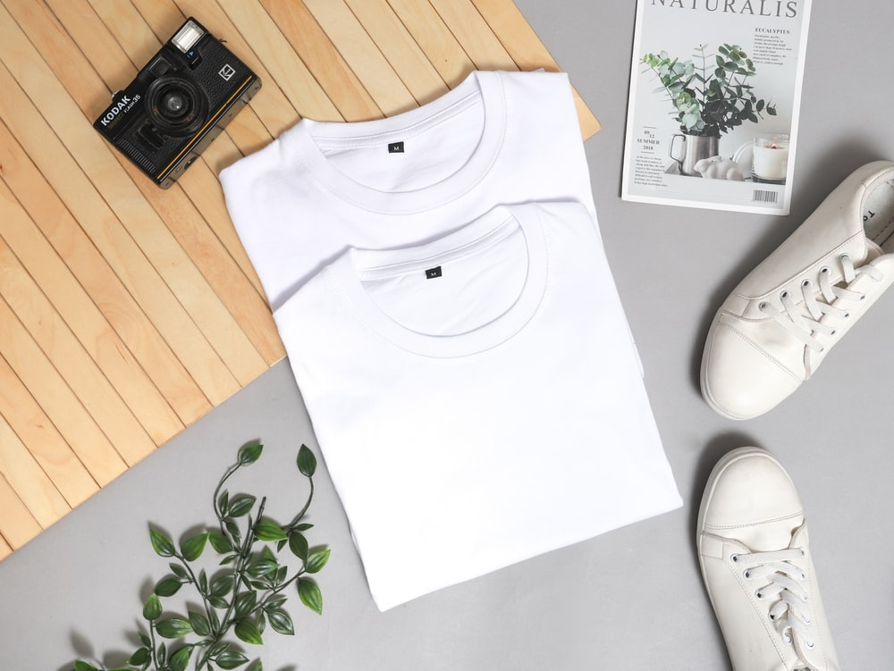 white crew neck shirt on white and green floral textile