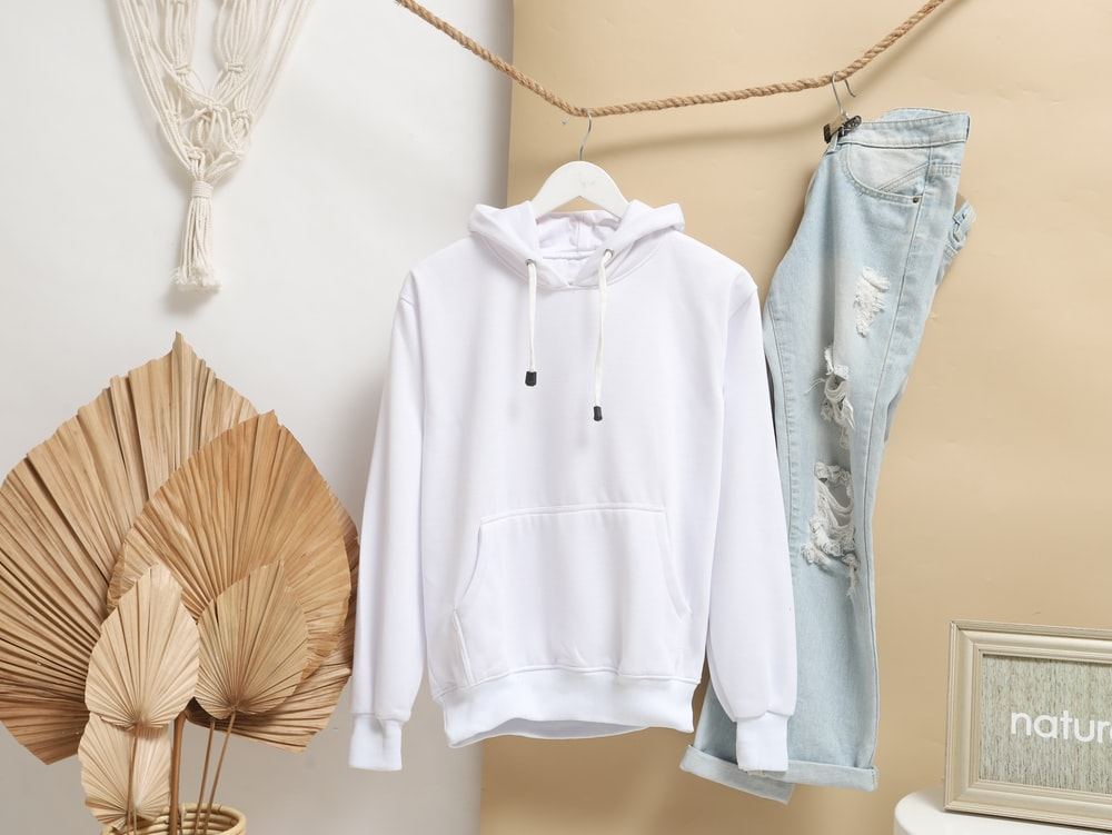 white zip up jacket hanging on brown wooden clothes hanger