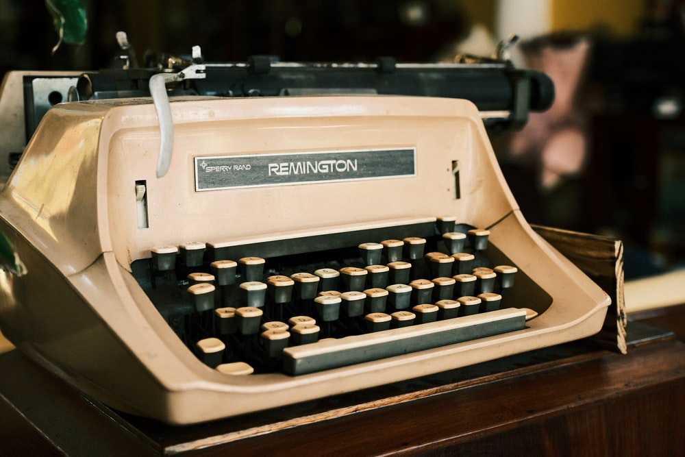 white and black typewriter on brown wooden table