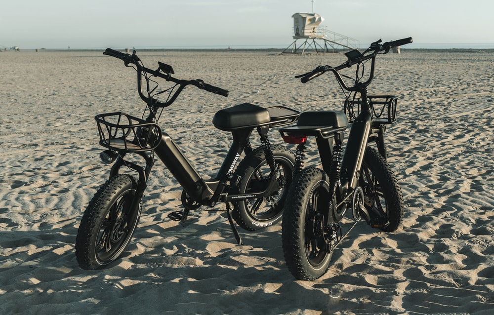 black and gray mountain bike on brown sand during daytime
