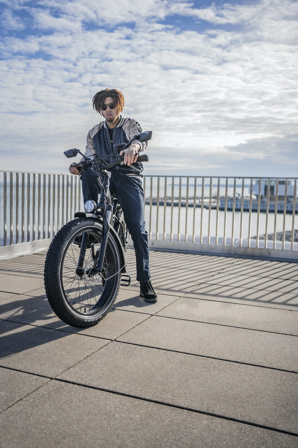 woman in black jacket and blue denim jeans riding bicycle during daytime