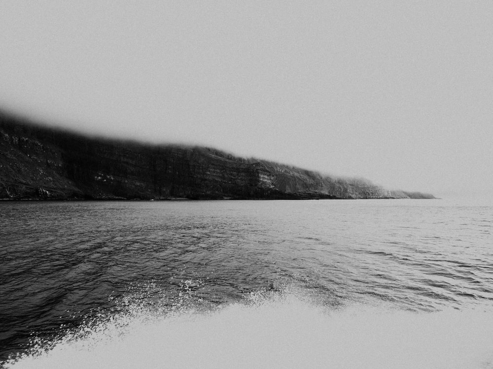grayscale photo of ocean near mountain