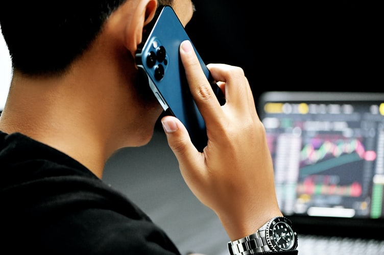 a cryptocurrency trader on the phone reviewing data