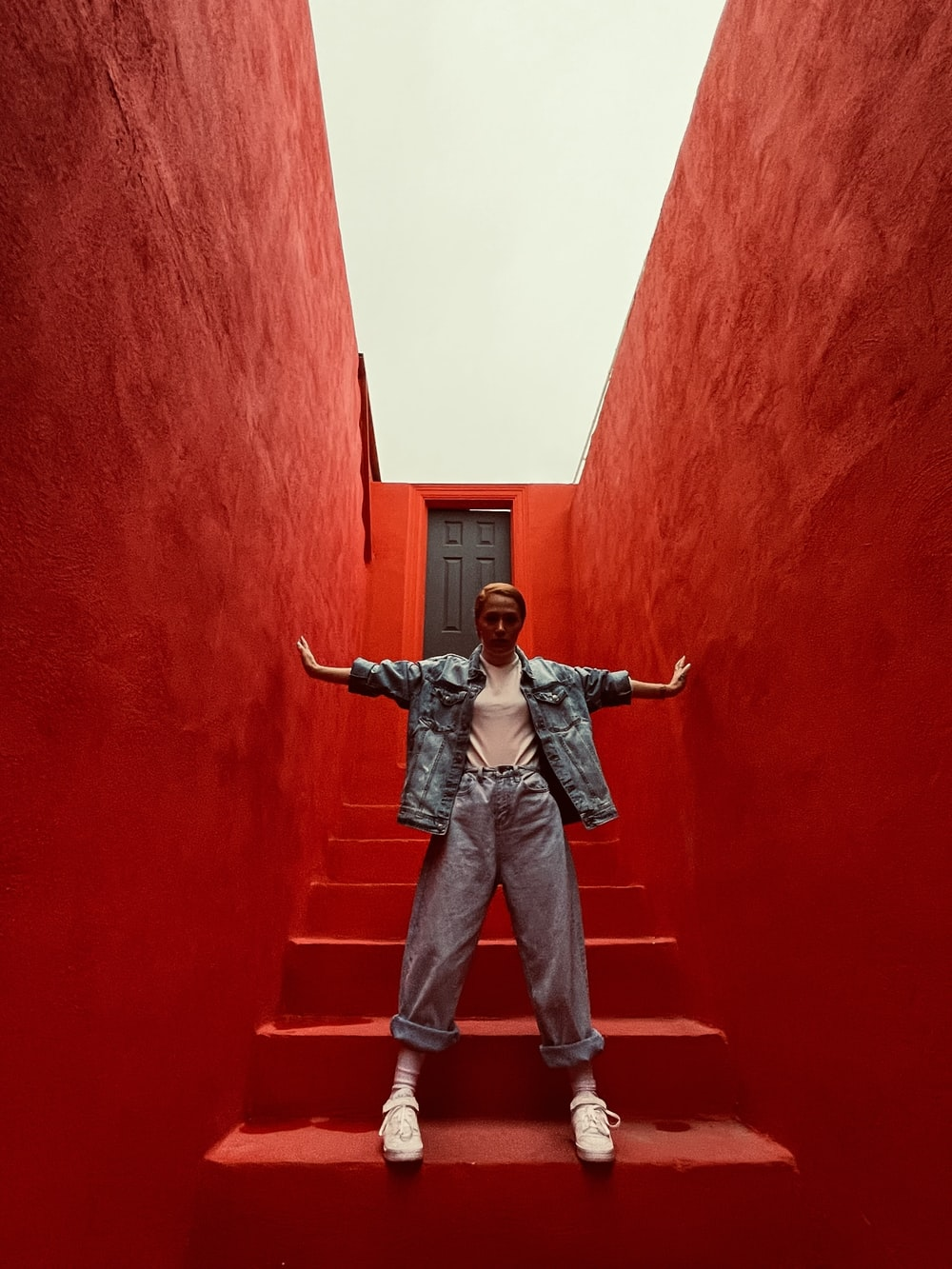 man in black jacket and blue denim jeans standing on red concrete wall