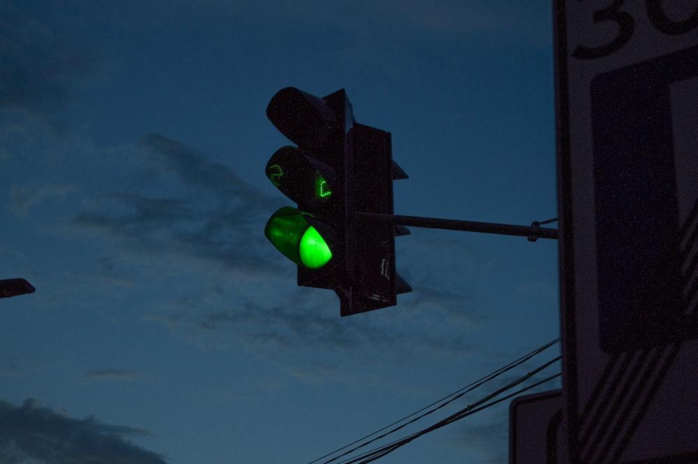 green traffic light under blue sky