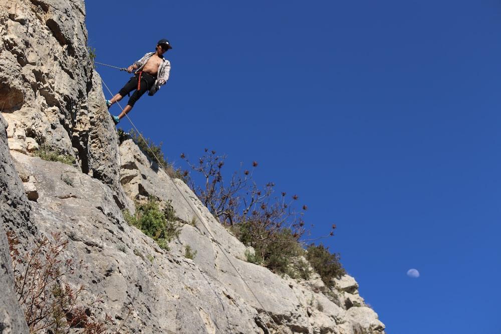 man in blue jacket climbing on rocky mountain during daytime