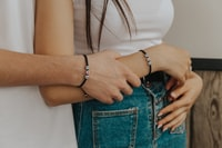 woman in white tank top and blue denim jeans