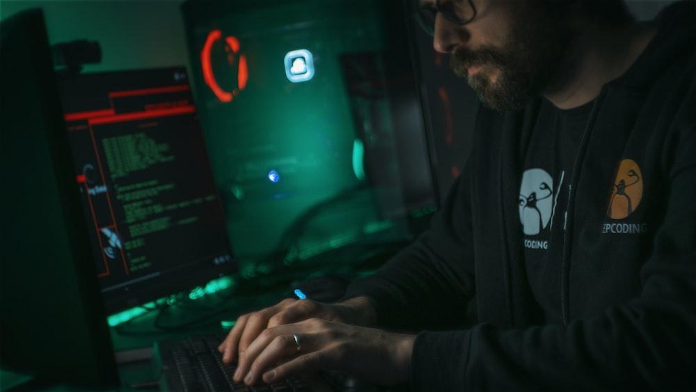 man in black jacket using computer