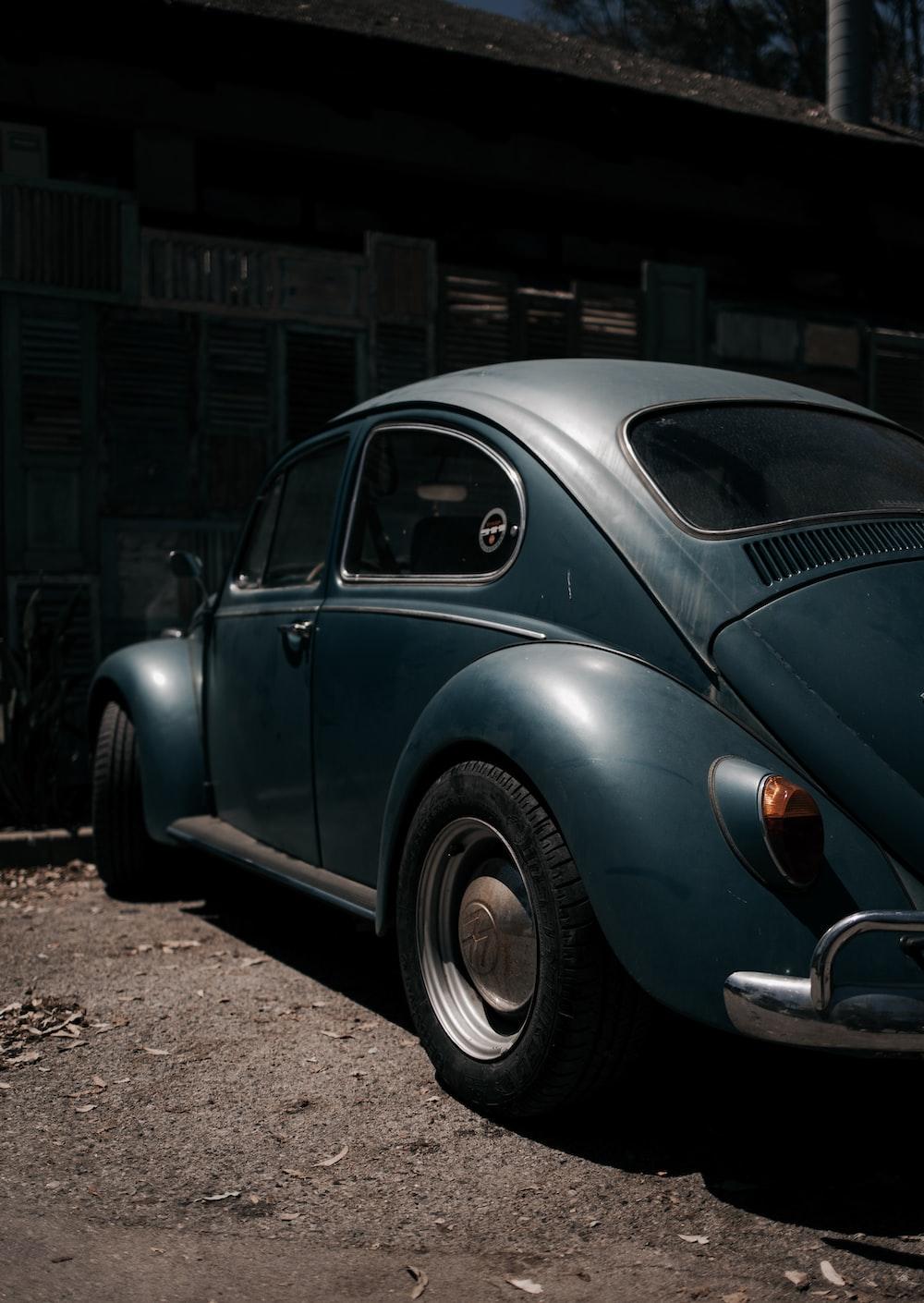 blue volkswagen beetle parked near building
