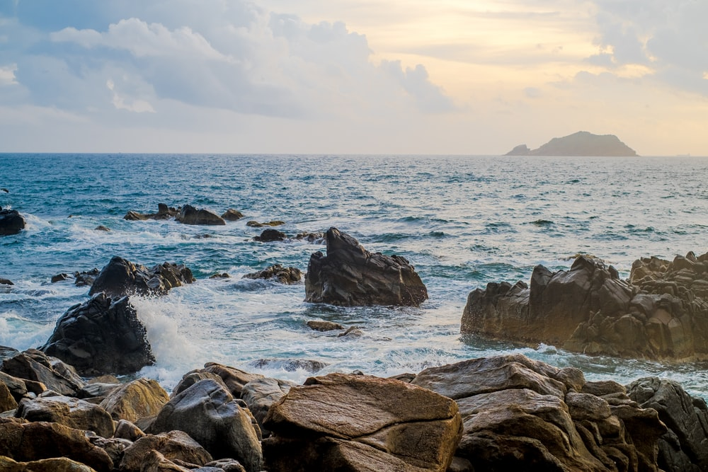 rocky shore with ocean waves under white clouds during daytime