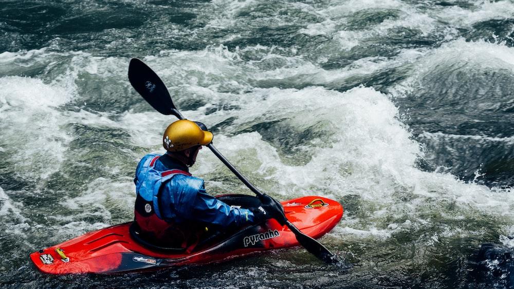 man in blue jacket riding red kayak on sea during daytime