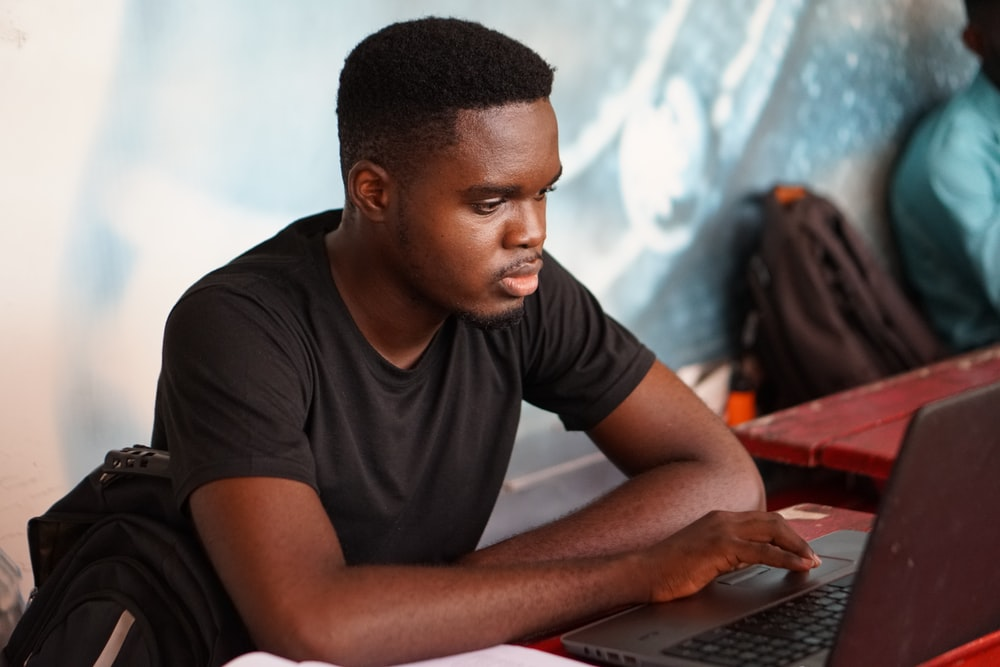 man in gray crew neck t-shirt using laptop computer