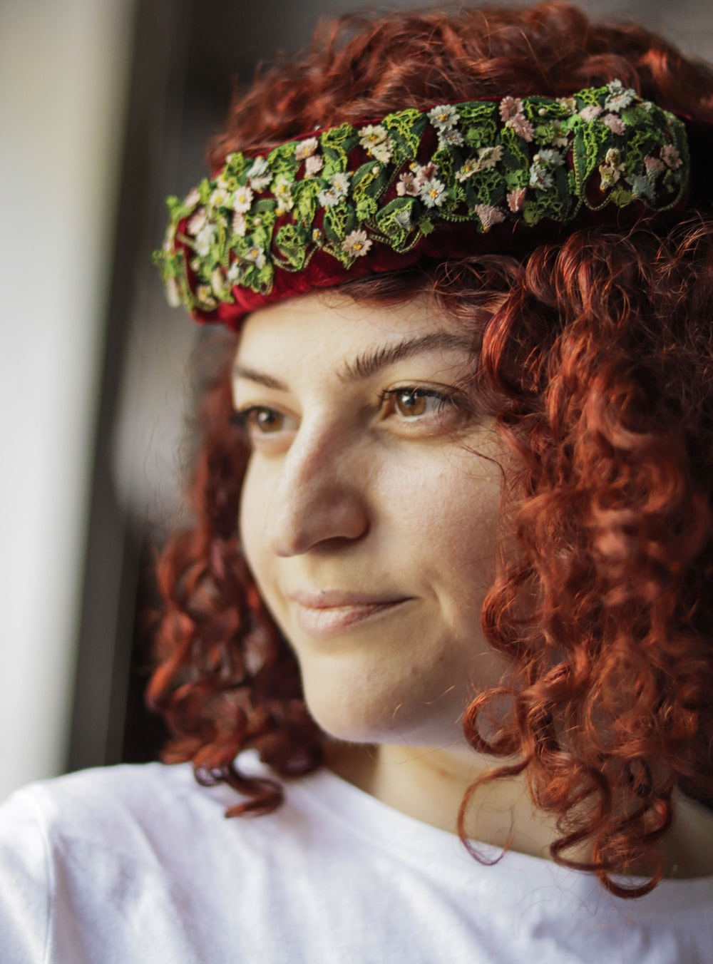 woman in white shirt wearing green and brown floral headdress
