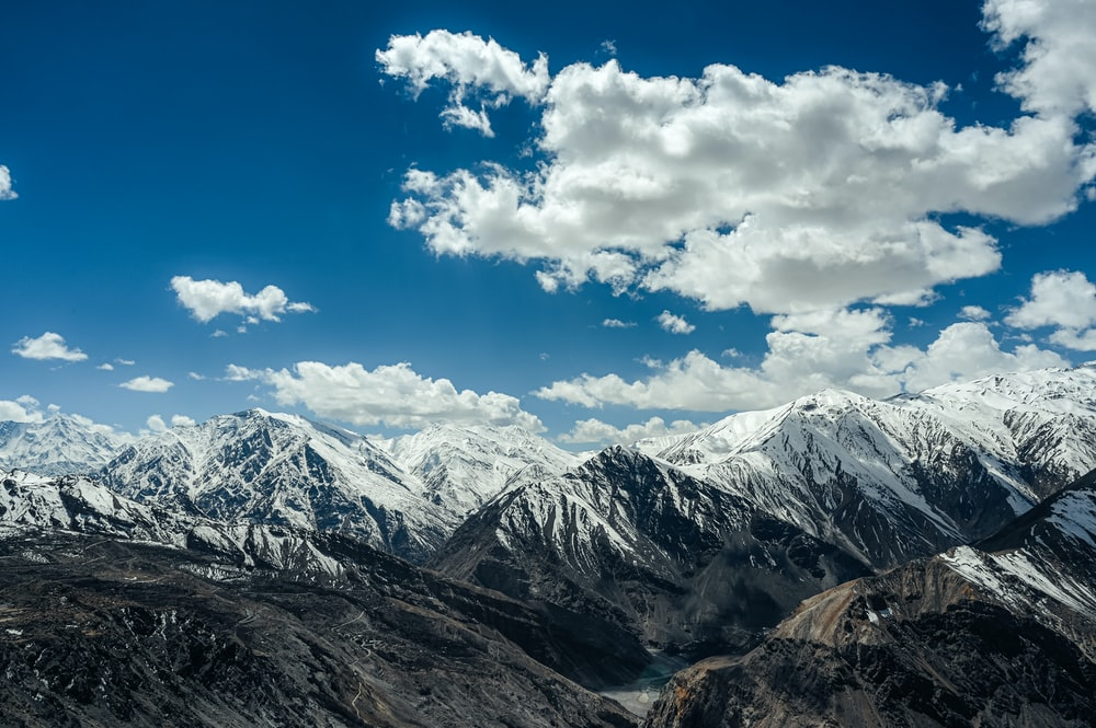 snow covered mountains under blue sky and white clouds during daytime