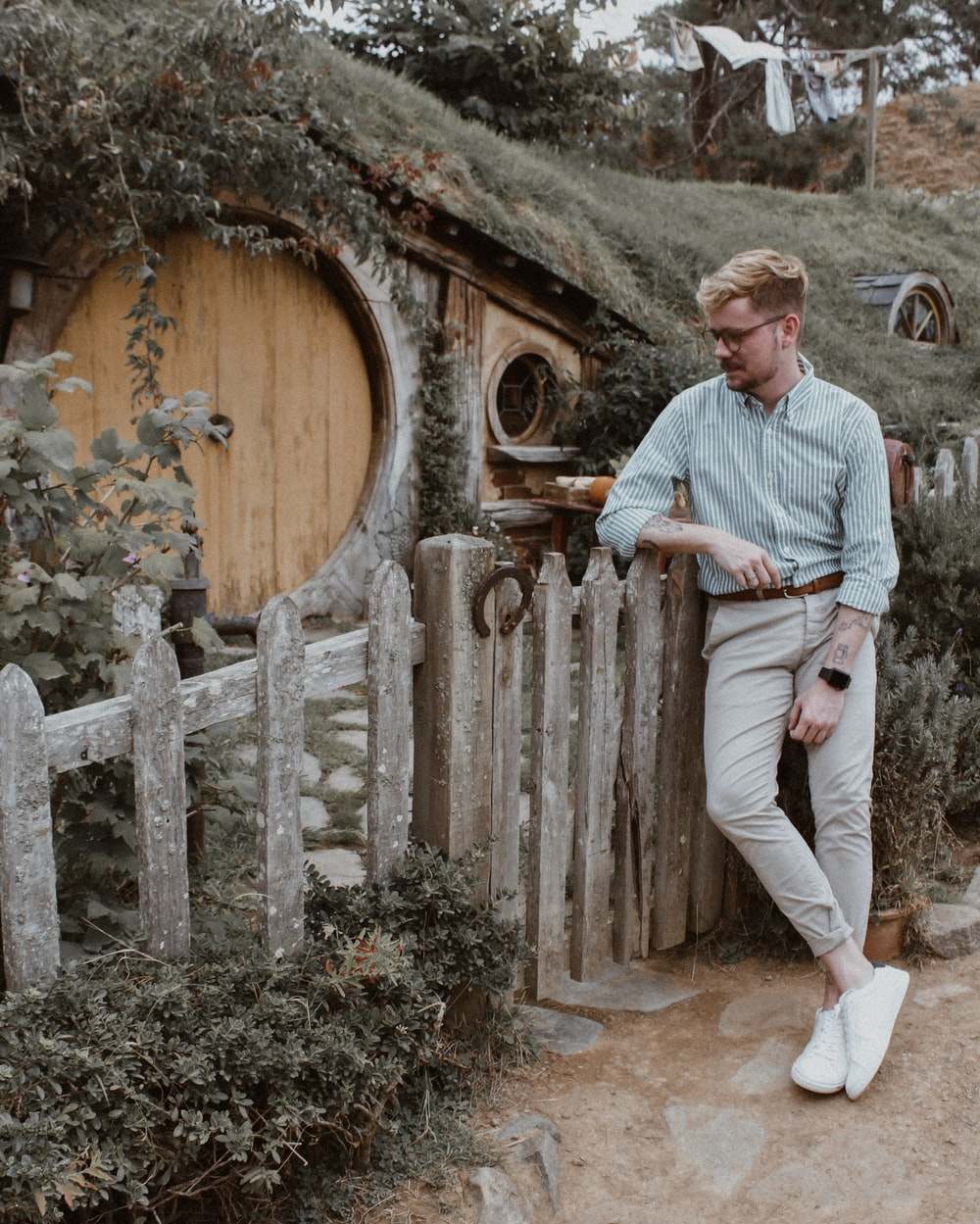 man in blue dress shirt and white pants sitting on brown wooden fence