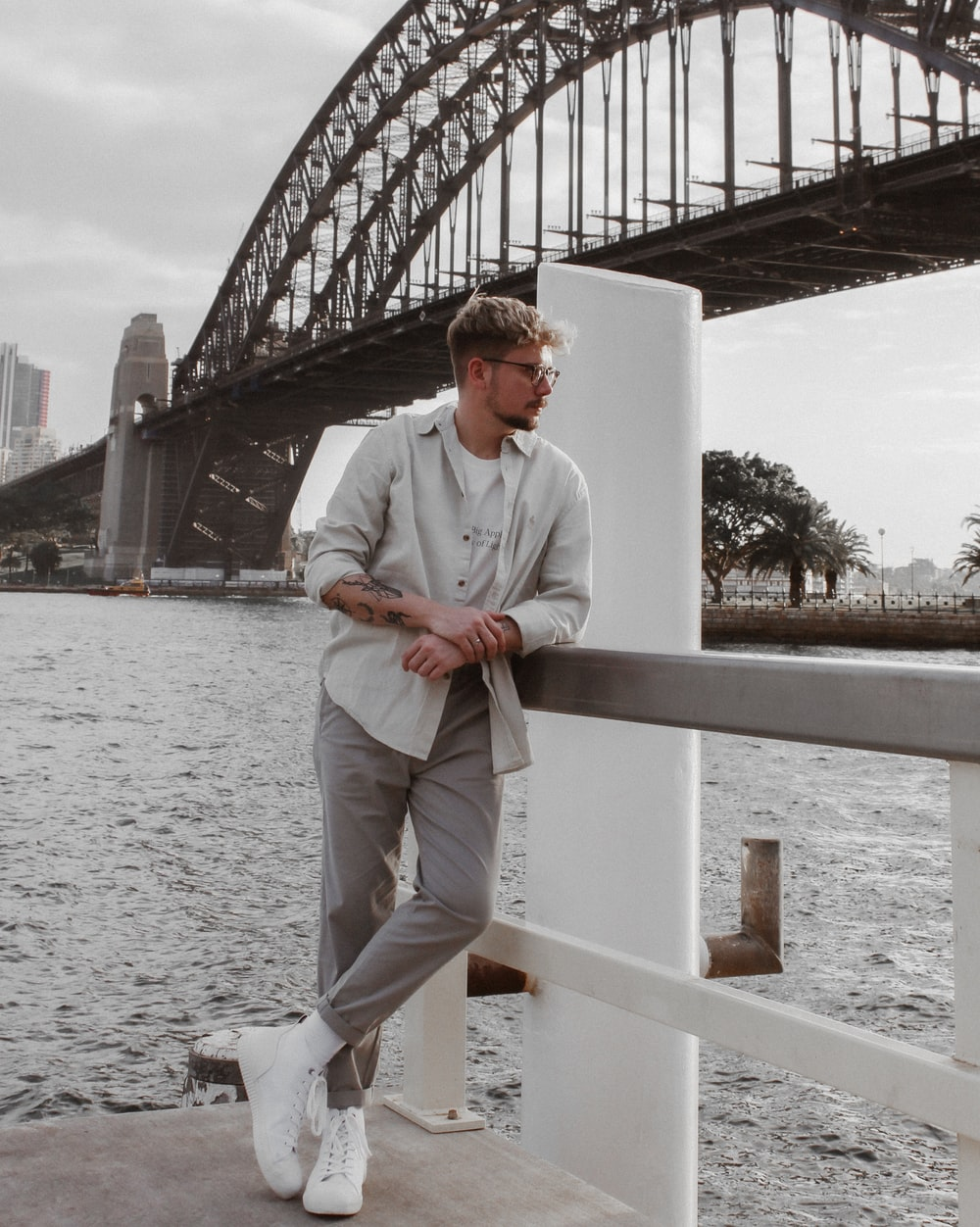 man in white dress shirt and white pants sitting on white wooden fence during daytime