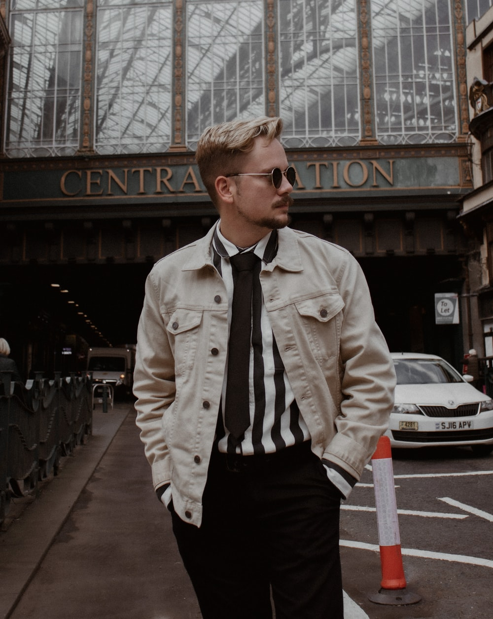 man in beige button up jacket and black pants standing on sidewalk during daytime
