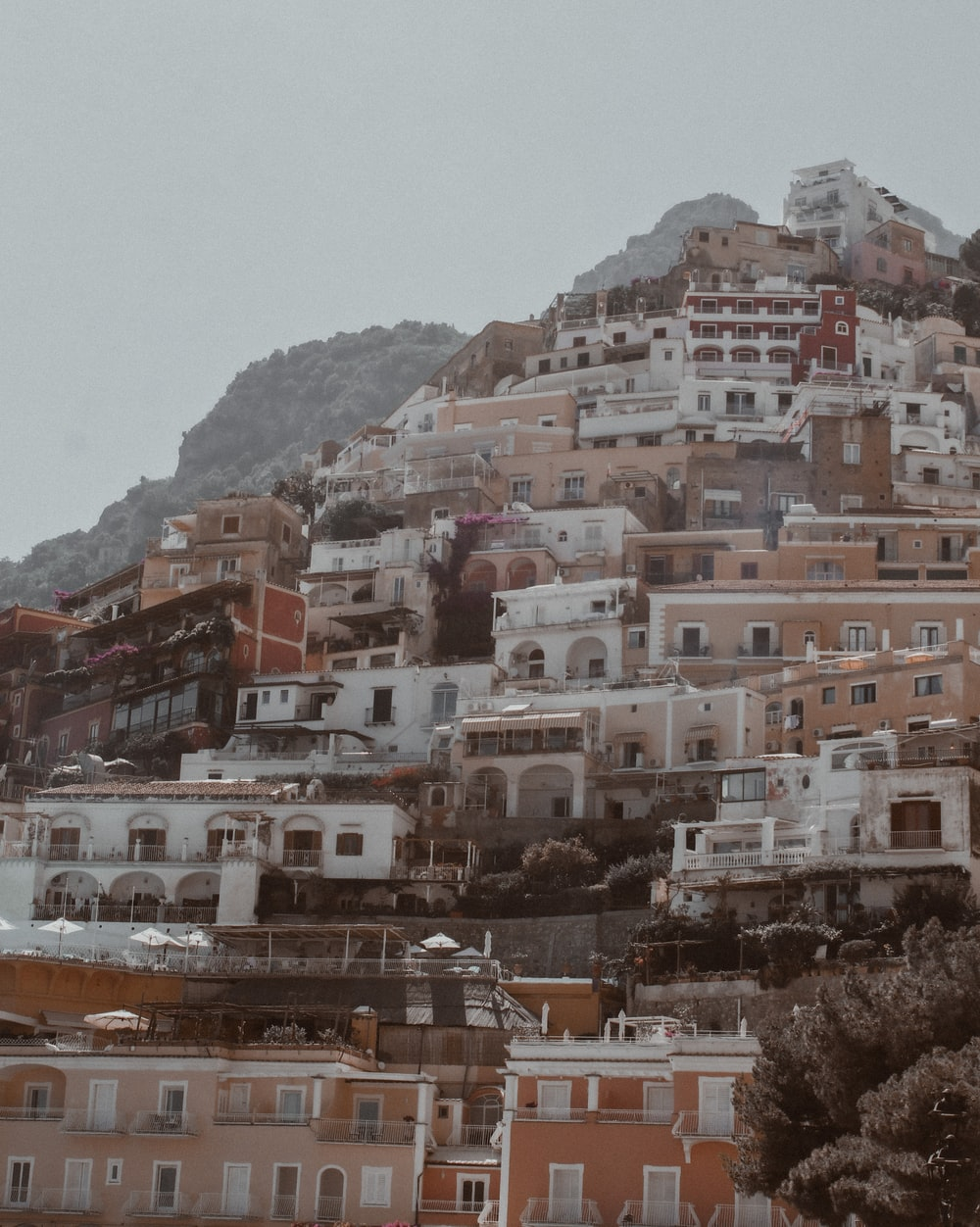 white and brown concrete buildings near mountain during daytime