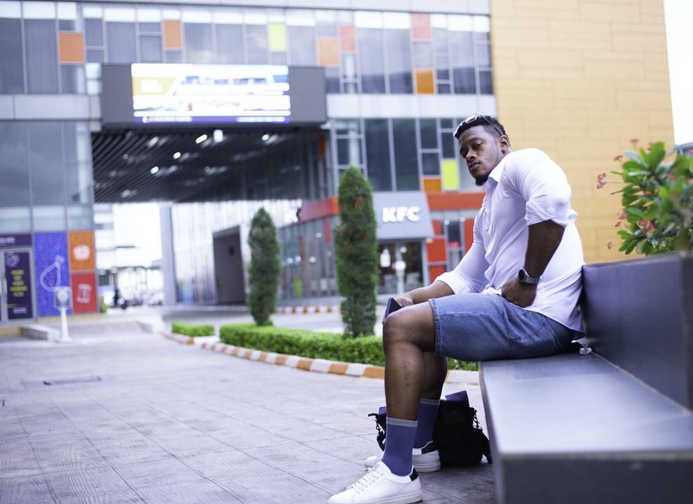 man in white dress shirt sitting on black bench during daytime