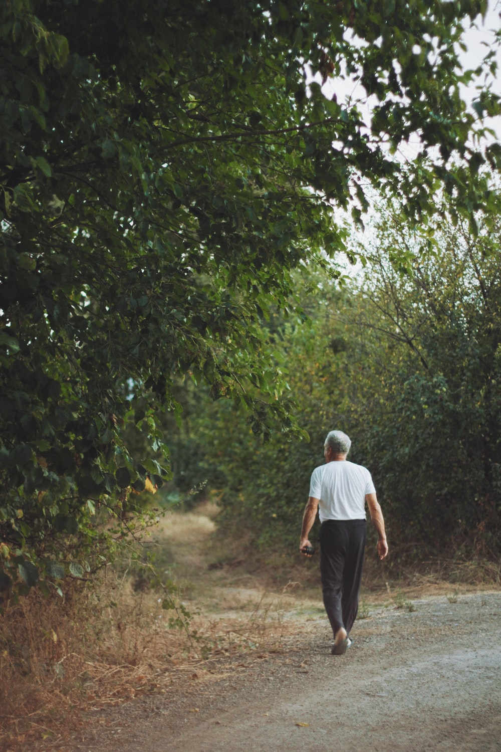 man in white shirt and black pants walking on dirt road