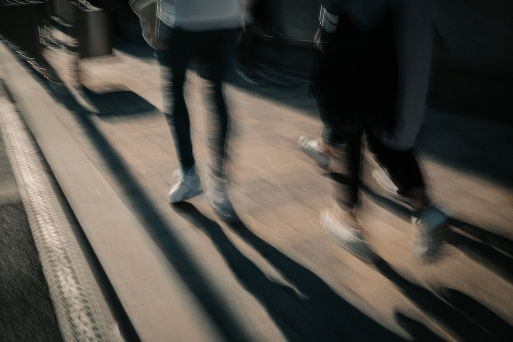 person in white shirt and blue denim jeans walking on sidewalk