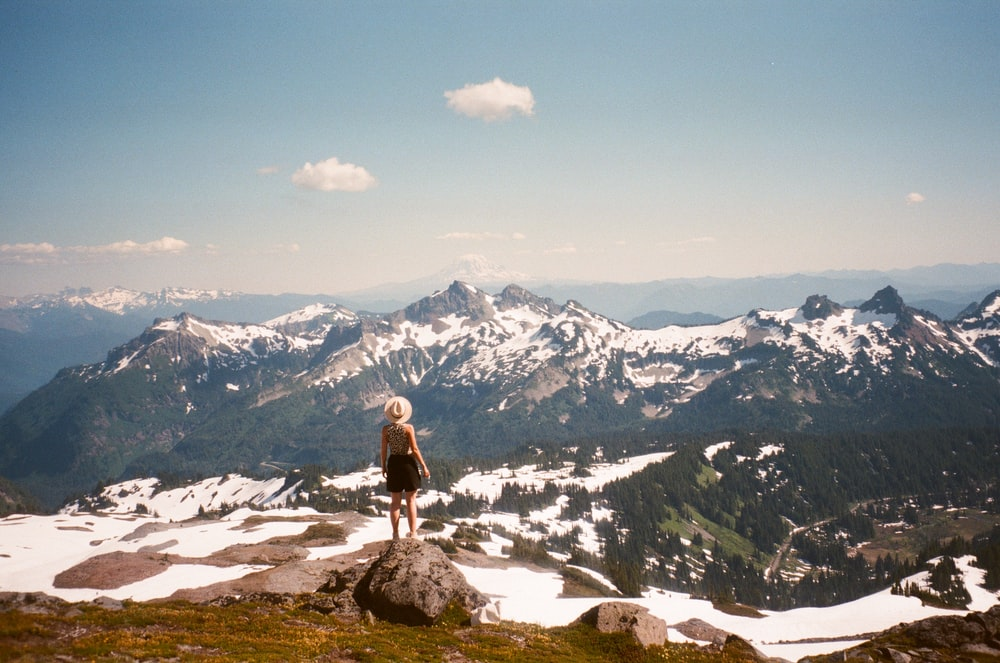 woman in white shirt and black pants standing on rock near snow covered mountains during daytime