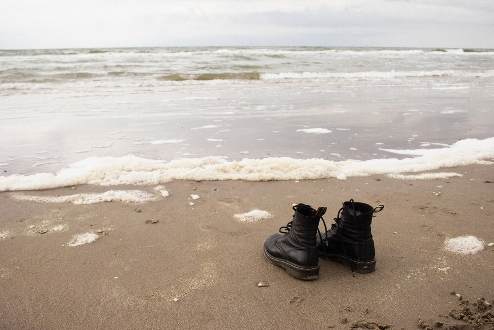 black leather boots on brown sand beach