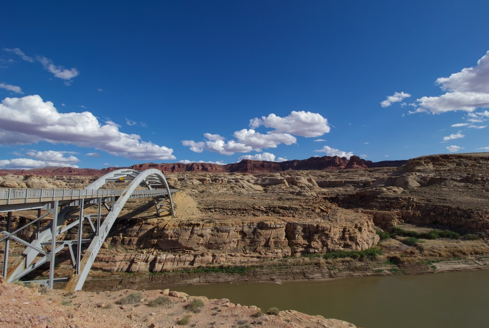 white metal bridge on brown rocky mountain under blue sky during daytime