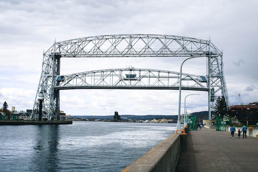 gray metal bridge over river under white sky during daytime