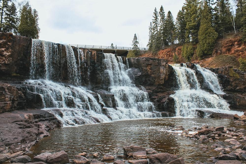 waterfalls near green trees under white sky during daytime