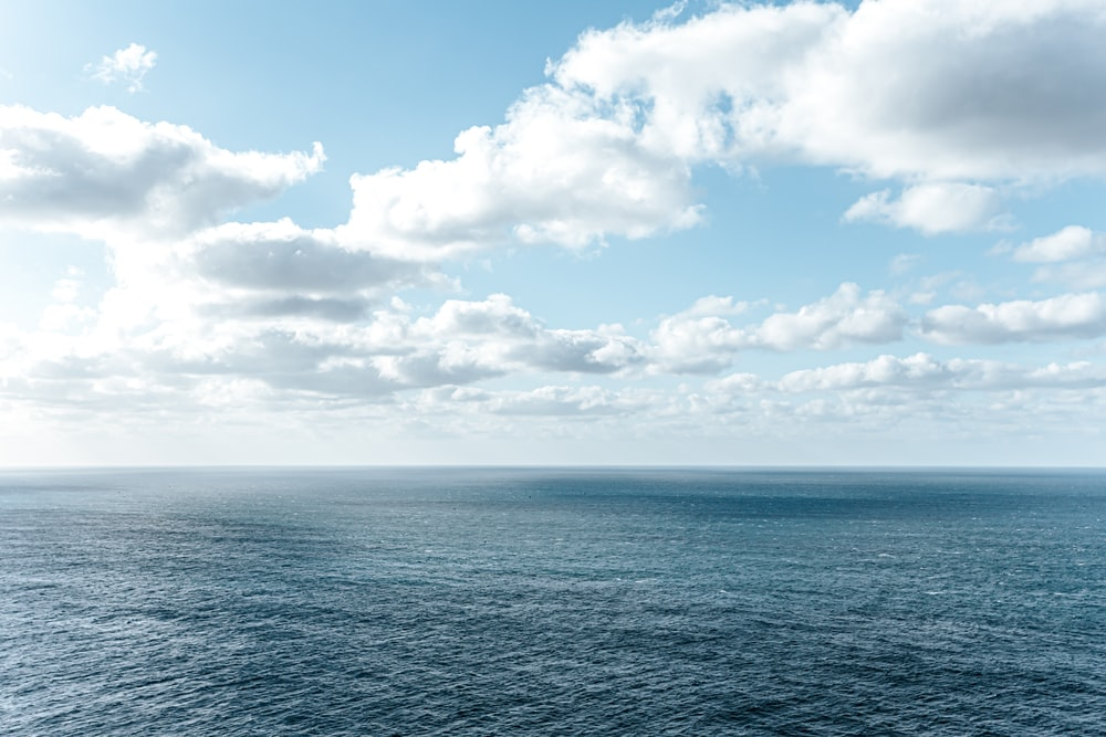 blue ocean under blue and white cloudy sky during daytime