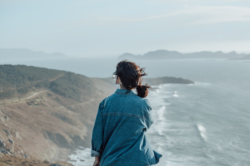 woman in blue denim jacket standing on cliff during daytime