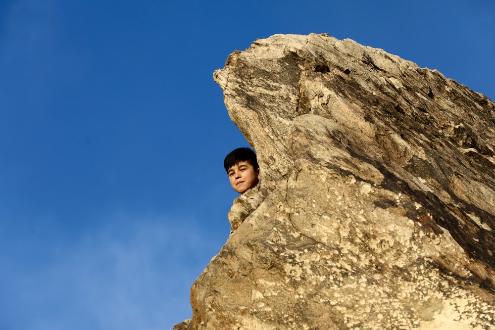woman in brown jacket standing on rock formation under blue sky during daytime