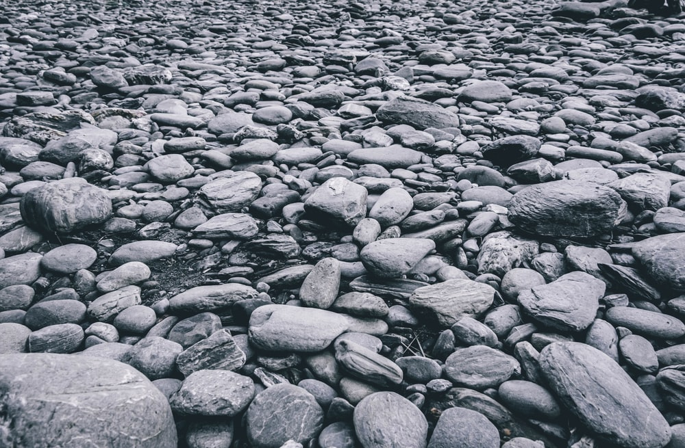 gray and black stones on body of water