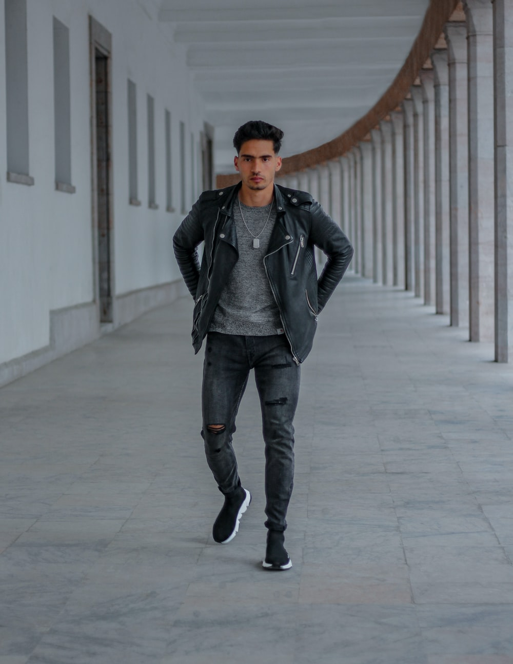 man in black leather jacket and blue denim jeans standing on white concrete floor