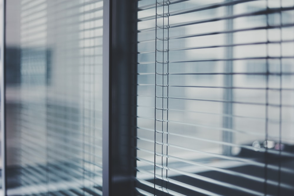 black framed glass window with white window blinds