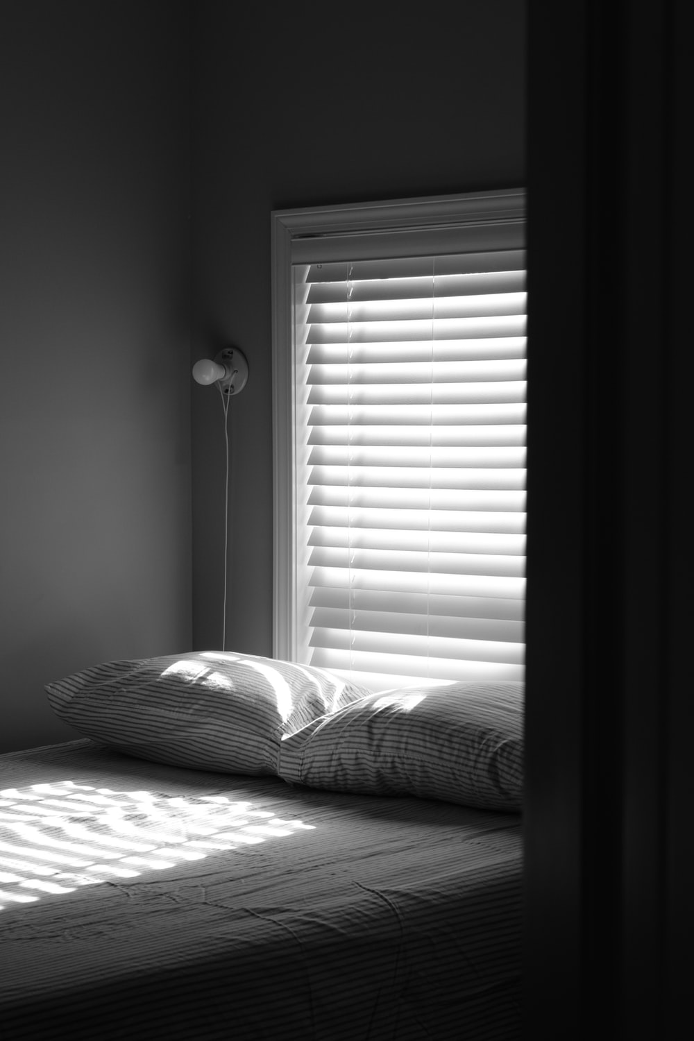 grayscale photo of bed with pillows