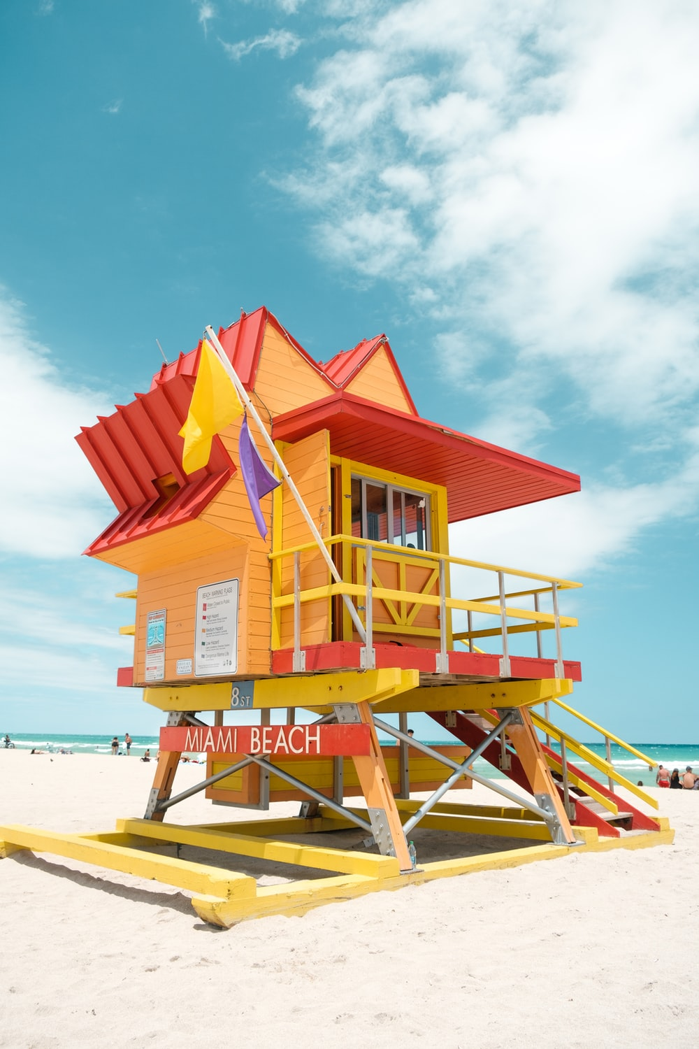 red and white wooden lifeguard house on beach shore during daytime