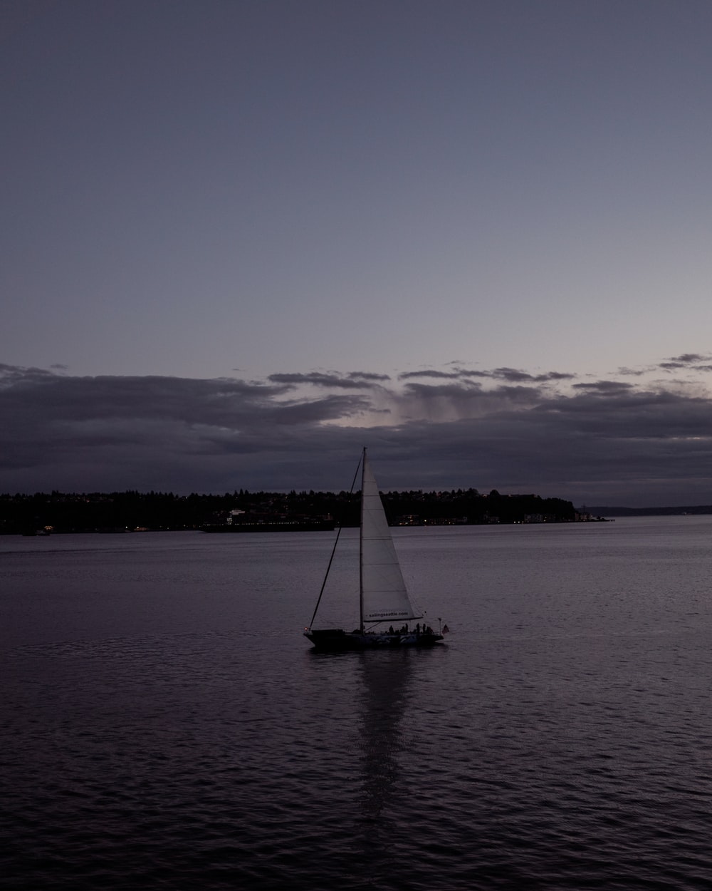 white sailboat on calm water during daytime