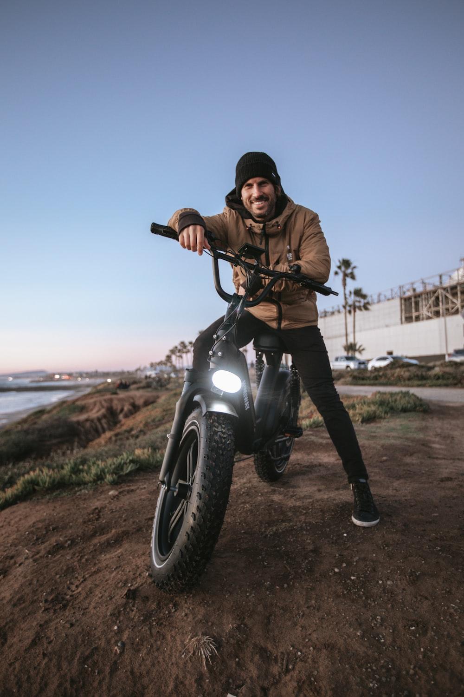 man in brown jacket riding black motorcycle during daytime