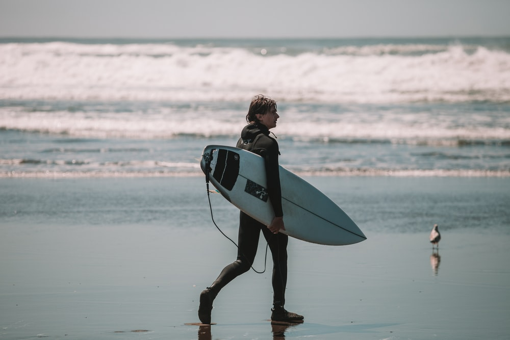 woman in black and white wetsuit holding white surfboard on beach during daytime