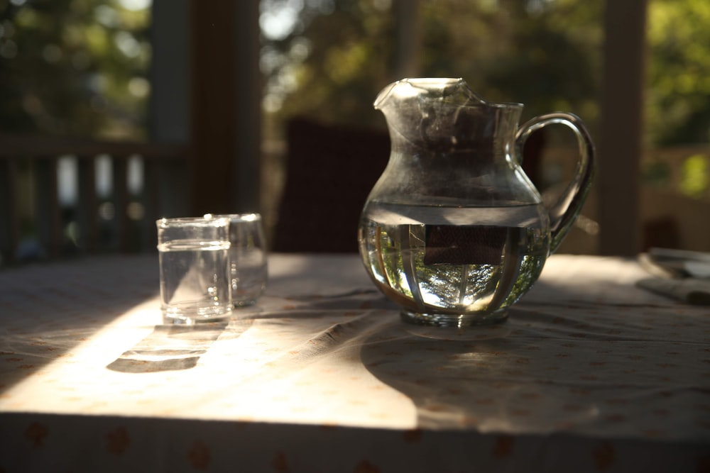 clear glass pitcher beside clear drinking glass on table
