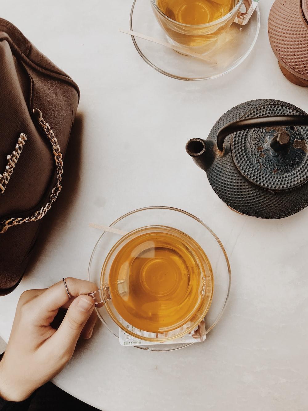 black ceramic teapot on white ceramic saucer