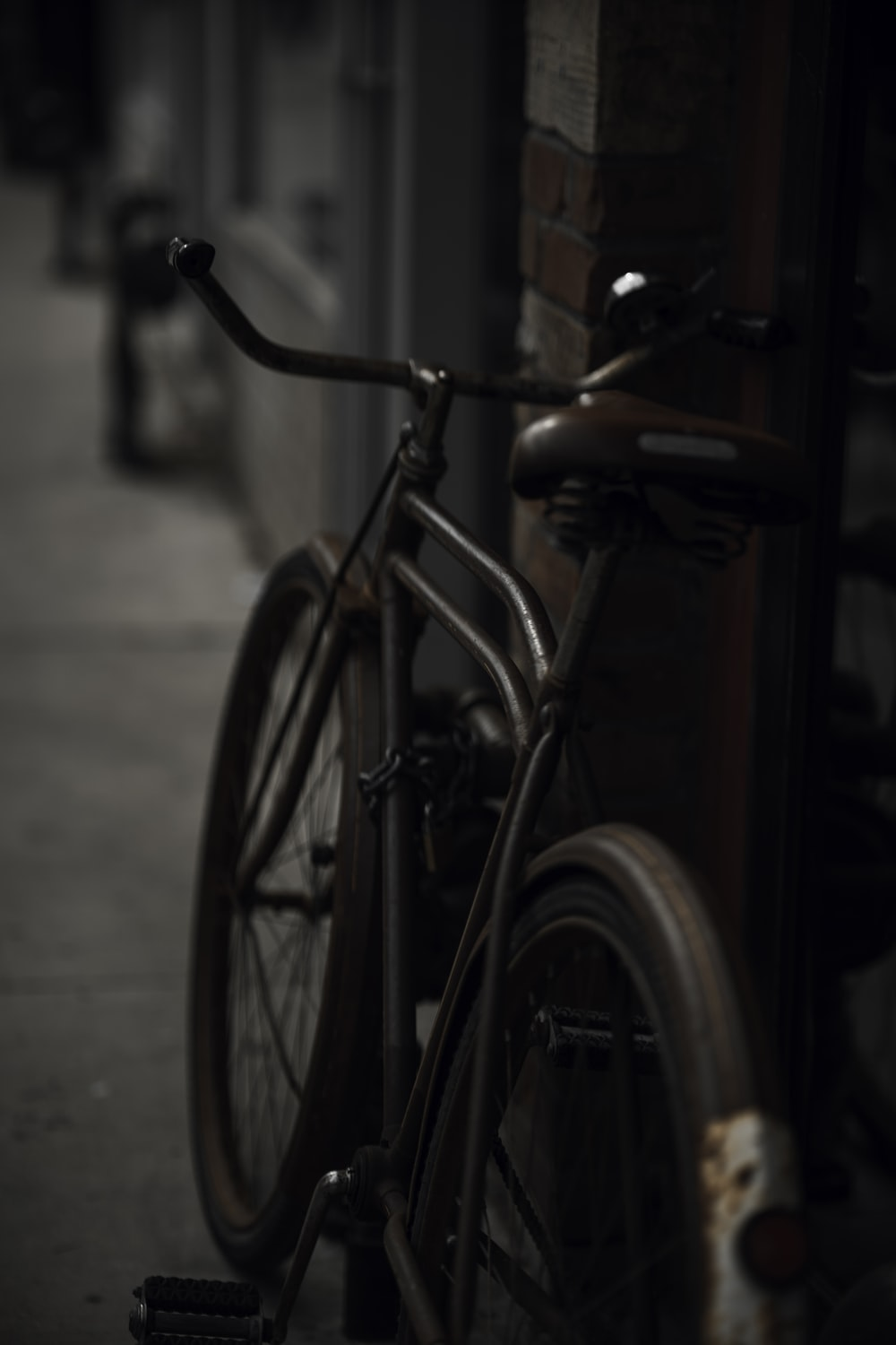 black city bike parked beside brown wooden wall