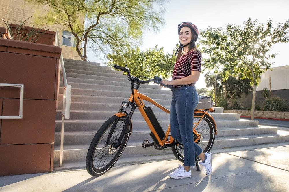 Woman with helmet next to her orange electric bike